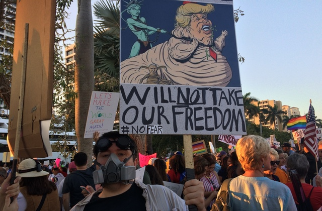 Protestors carry Anti-Trump signs outside Mar-A-Lago, Feb. 4