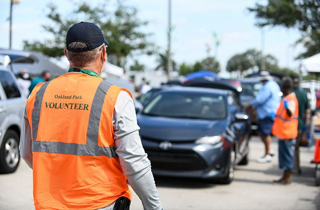 A volunteer with the City of Oakland Park directs traffic at Mills Pond Park. Photo credit: Carina Mask.